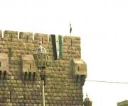 Damasco, 21-12-2011. La bandiera siriana usata prima dell'avvento del Baath nel 1963 spunta dai merli delle antiche mura della cittadella medievale (Reuters)