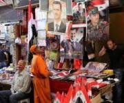 Un operaio guarda i poster di Asad in vendita a Damasco