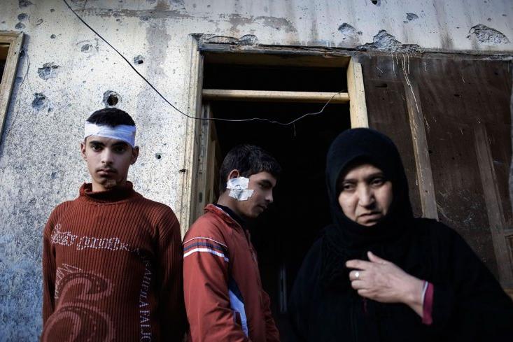 Una donna con i figli di fronte alla loro casa distrutta dall'esercito siriano