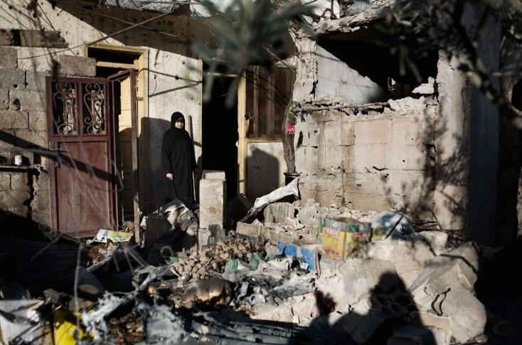 Una donna tra le macerie della sua casa distrutta dall'esercito siriano