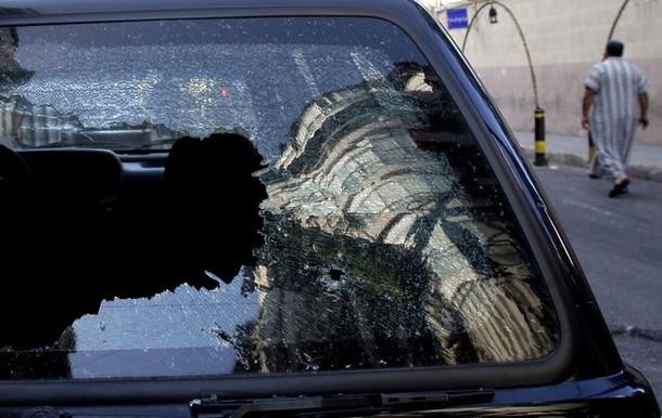 A Lebanese man walks past a bullet riddl