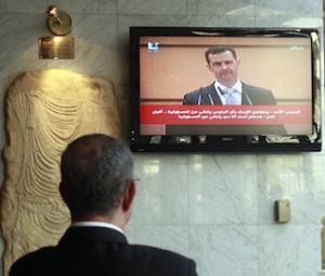 Concierge di un albergo di Damasco ascolta il discorso di Bashar al Assad, EPA/Badawi, Damasco, 10 gennaio 2012