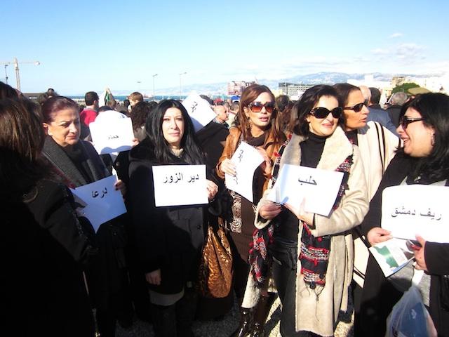 Donne che manifestano mostrando fogli con i nomi delle città colpite dalla repressione, Beirut 17 marzo (Jessica C.)