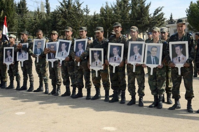 SANA picture shows forces loyal to Syria's President Assad carrying pictures of him and his late father at an undisclosed location