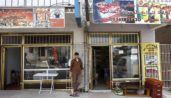 A Syrian man who had fled the war in his homeland stands outside shops run by Syrians in a low-income neighborhood of Ankara